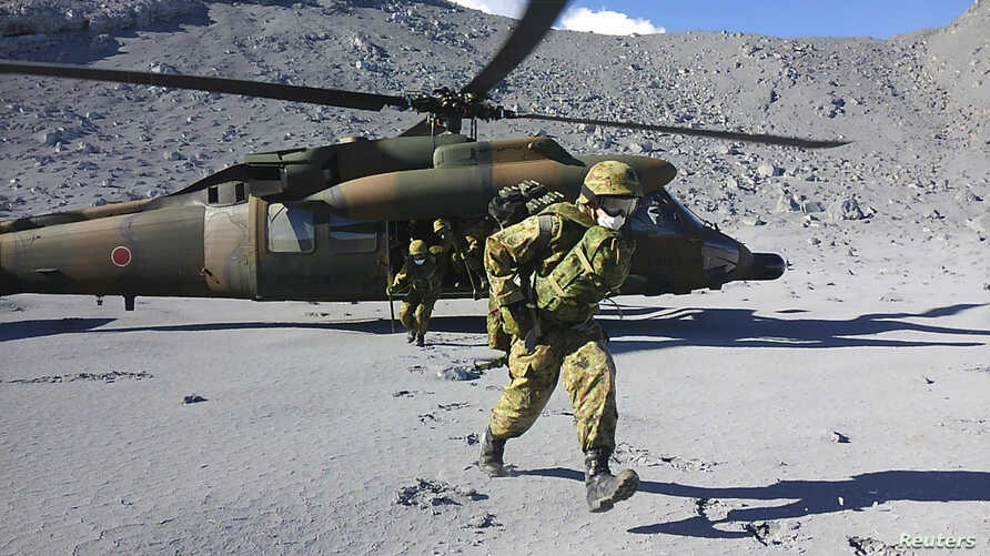 Japan Self-Defense Force (JSDF) soldiers run after landing in a helicopter for a rescue operation near the peak of Mt. Ontake, which straddles Nagano and Gifu prefectures, central Japan, in this handout photograph released by Joint Staff of the Defen...