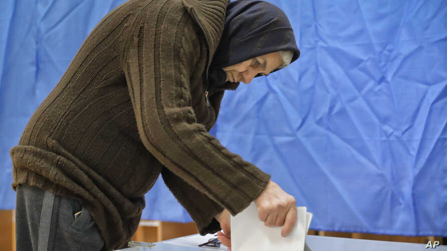 A voter casts a ballot in Targusoru Nou, Romania, Dec. 11, 2016. Romanians began voting Sunday in a parliamentary election a year after a massive anti-corruption drive forced the last Socialist prime minister from power.