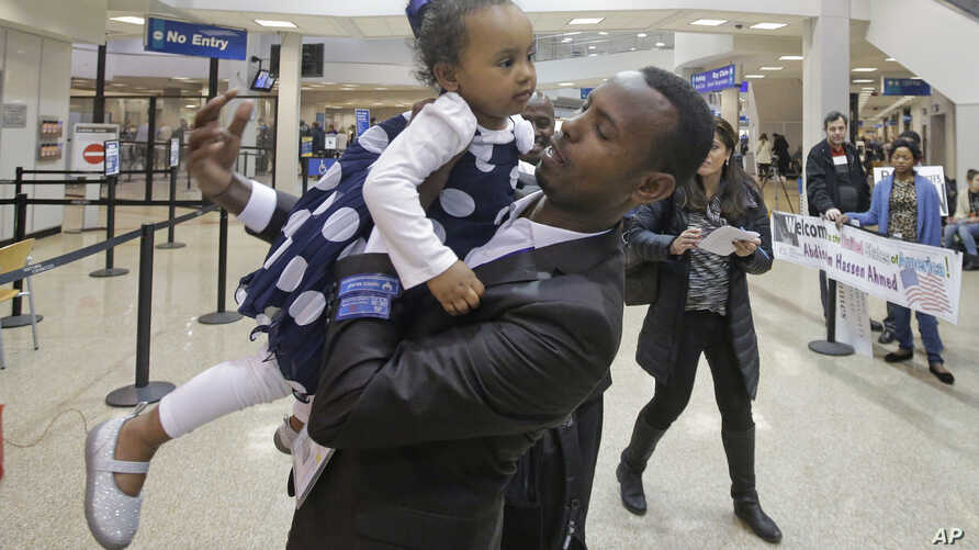 Abdisellam Hassen Ahmed, a Somali refugee who had been stuck in limbo after President Donald Trump temporarily banned refugee entries, holds his 2-year-old daughter, Taslim, after meeting her for the first time upon arriving at Salt Lake Internationa