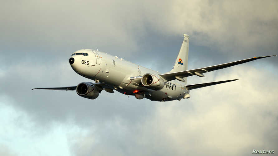 A P-8A Poseidon surveillance plane conducts flyovers above the Enterprise Carrier Strike Group on February 3, 2012 in this handout photo courtesy of the U.S. Navy.
