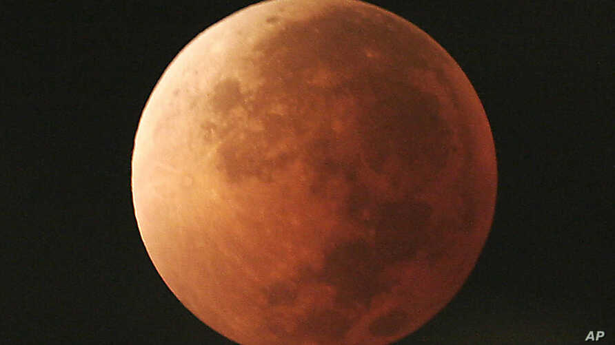 FILE - In this Aug. 28, 2007, file photo, the moon takes on different orange tones during a lunar eclipse seen from Mexico City. On  Jan. 31, 2018, a super moon, blue moon and a lunar eclipse will coincide for first time since 1982 and will not occur