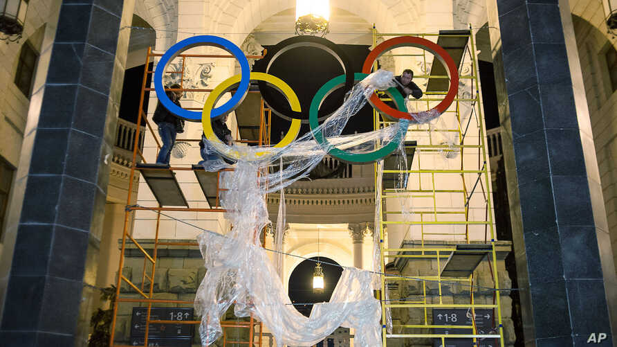 In this Oct. 28, 2013 photo, workers fix the Olympic emblem at an entrance to the railway station of Russia's Black Sea resort of Sochi, Russia.