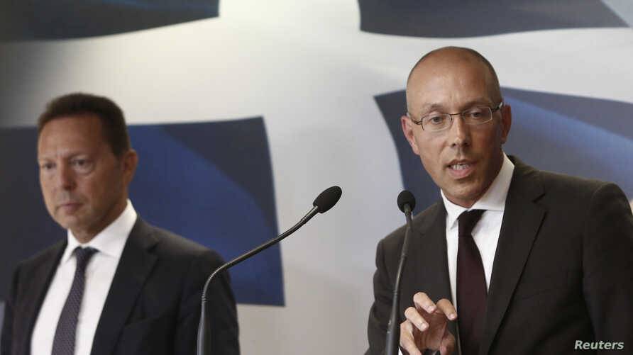 European Central Bank (ECB) executive board member Joerg Asmussen (R) addresses reporters next to Greece's Finance Minister Yannis Stournaras during a news conference in Athens, Greece, Aug. 21, 2013.