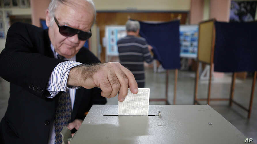 A man votes in the presidential election in southern port city of Limassol, Cyprus, February 24, 2013.