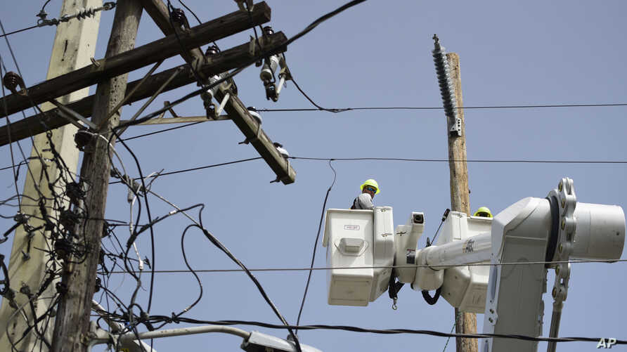 FILE - A brigade from the Puerto Rico Electric Power Authority repairs distribution lines damaged by Hurricane Maria in the Cantera community of San Juan, Puerto Rico, Oct. 19, 2017. The storm struck after the authority had filed for bankruptcy in Ju