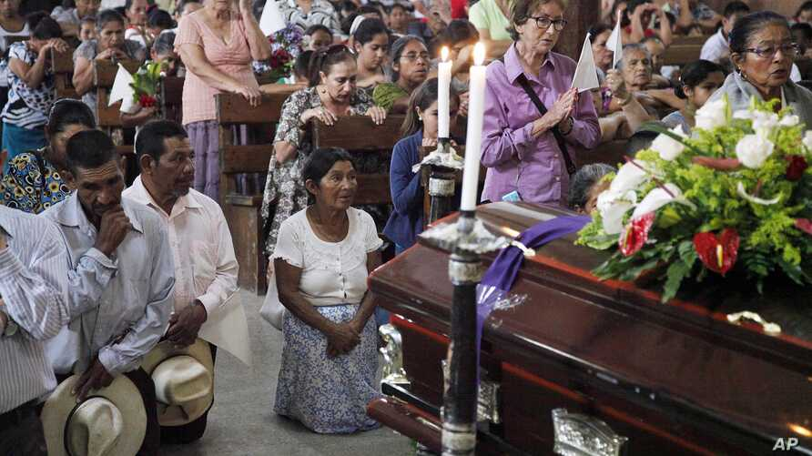 People pray by the coffin of slain Janeth Urquia, an environmentalist and indigenous rights activist, during Mass in Marcala, Honduras, July 8, 2016.