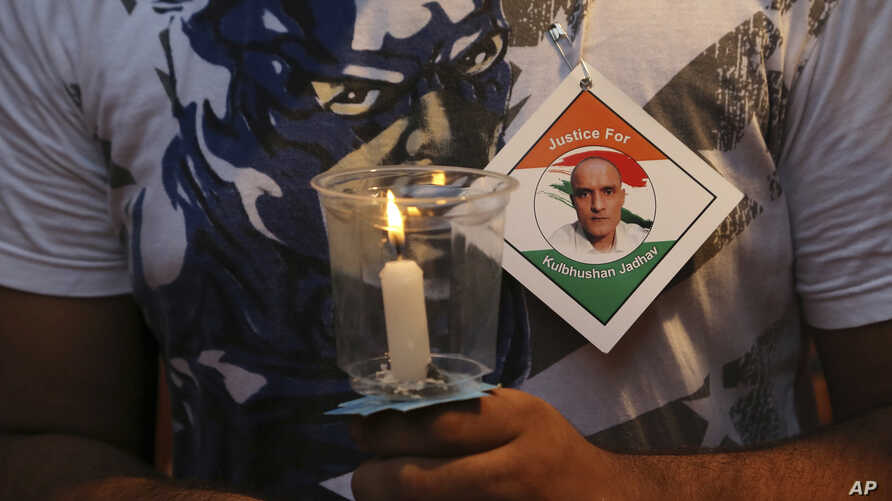 FILE - An Indian man holds a candle as he participates in a demonstration in support of Indian naval officer Kulbhushan Jadhav in Mumbai, India, June 03, 2017.