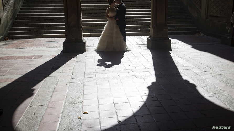 FILE - Jun Liu poses for a photo with his bride Seogyeong Choi during a wedding photoshoot at Bethesda Terrace in the Manhattan borough of New York, Oct.  20, 2015.