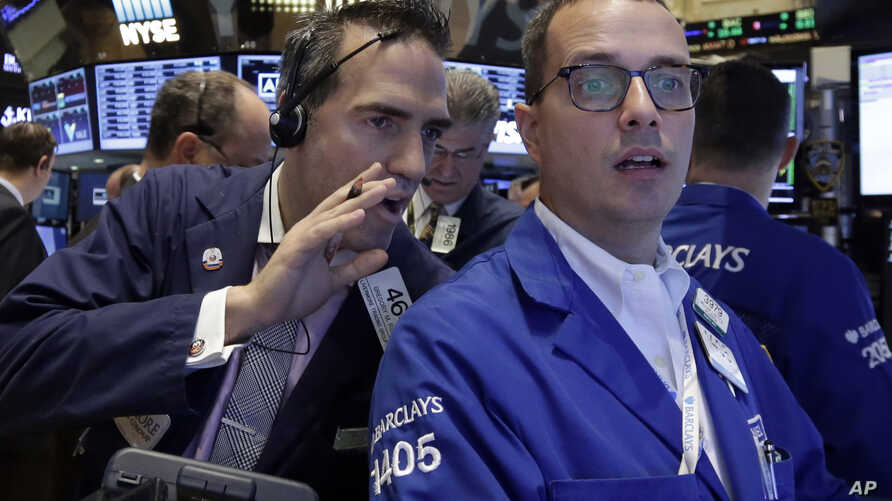 Trader Gregory Rowe, left, talks to specialist Neil Gallagher as they work on the floor of the New York Stock Exchange, Aug. 28, 2015.