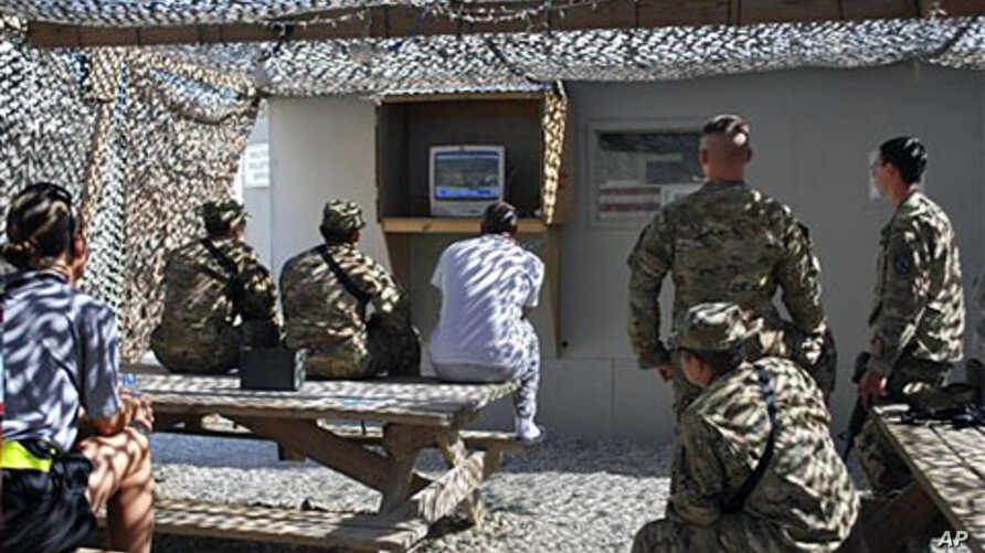 US troops watch cable news coverage of the death of al-Qaida leader Osama bin Laden at the Bagram air field, Afghanistan, May 2, 2011
