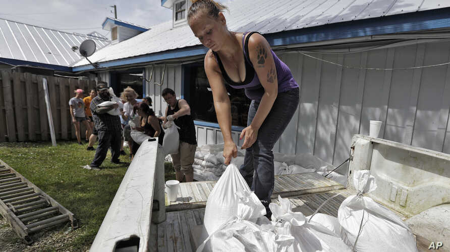 Krystal Day, of Homosassa, Fla., leads a sandbag assembly line at the Old Port Cove restaurant Tuesday, Oct. 9, 2018, in Ozello, Fla.