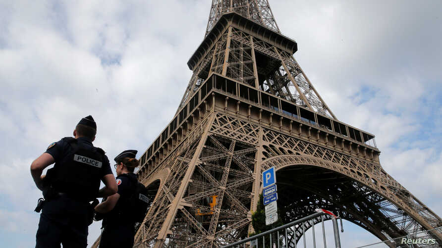 FILE - French police patrol near the Eiffel tower as part of security measures in Paris, France, July 13, 2017.