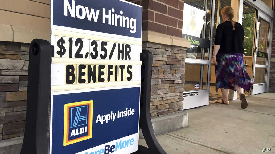 """FILE- A sign outside a business in Salem, New Hampshire, says """"Now Hiring."""" On Oct. 16, the Labor Department reports on job openings and labor turnover for August, July 17, 2018."""