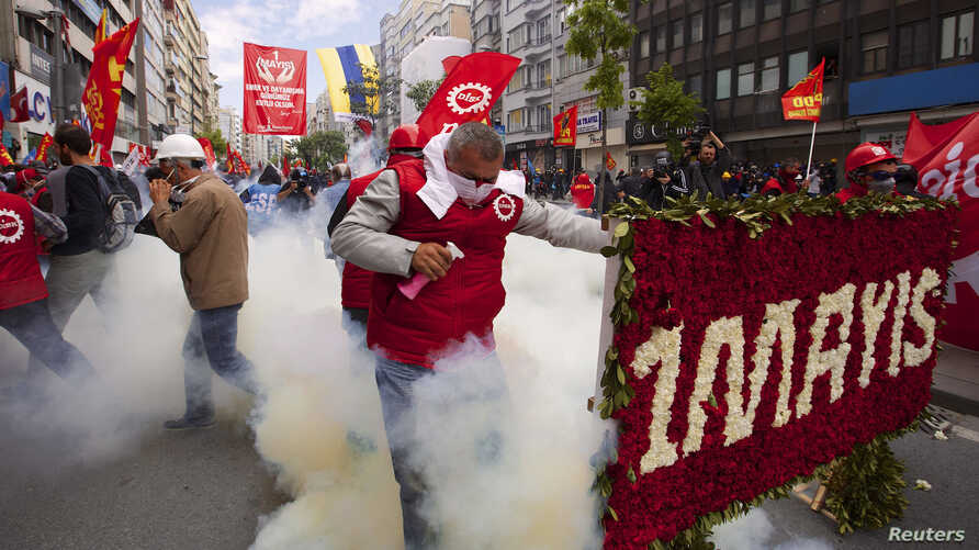 A protester reacts as police fires tear gas during a May Day demonstration in Istanbul May 1, 2014.