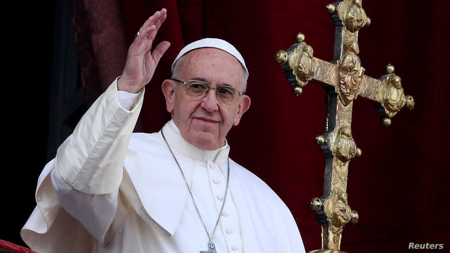 """Pope Francis waves after delivering his """"Urbi et Orbi"""" (to the city and the world) message from the balcony overlooking St. Peter's Square at the Vatican, Dec. 25, 2016."""