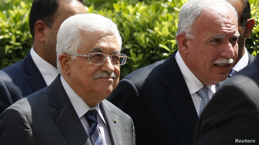 Palestinian President Mahmoud Abbas and his foreign minister Riyad al-Maliki (R) arrive for an Arab League Foreign Ministers emergency meeting at the league's headquarters in Cairo, Sept. 7, 2014.