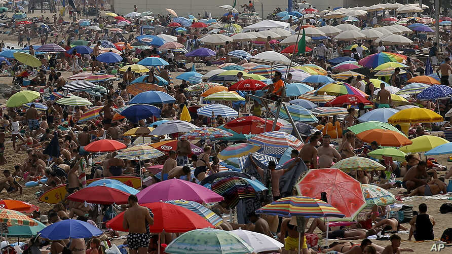 People sunbathe on a beach on a hot summer day in Barcelona, Spain, Aug. 4, 2018. Hot air from Africa is bringing a heat wave to Europe, prompting health warnings about Sahara Desert dust and exceptionally high temperatures that reached nearly 47 deg