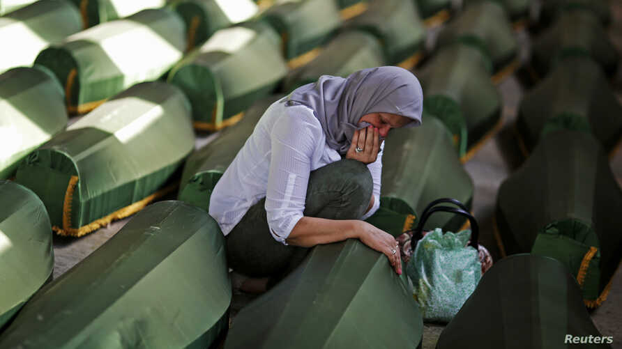 A Bosnian woman cries at a coffin of her relative, one of 173 coffins of newly identified victims from the 1995 Srebrenica massacre, in the Potocari Memorial Center, near Srebrenica, July 9, 2014.