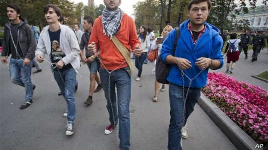 Symbolically chained Pussy Riot supporters march near the Kremlin Wall, Moscow, Sept. 22, 2012.