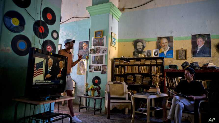 A man watches President Donald Trump's inauguration speech on television, as he sits next to photographs of Cuba's President Raul Castro, top right, Fidel Castro, top center, and Camilo Cienfuegos, in Havana, Jan. 20, 2017.