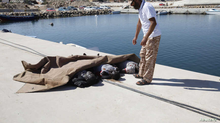 A man inspects the bodies of three African migrants that were recovered by the Libyan coastguard after their boat sunk off the coastal town of Garaboly, east of Tripoli, Sept. 15, 2014.