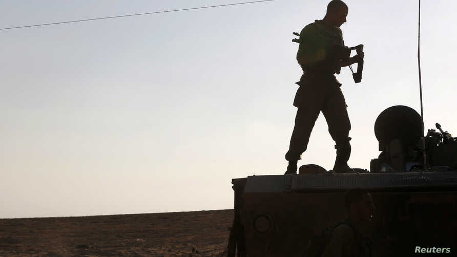 An Israeli soldier stands atop an armored personnel carrier (APC) near the border with the Gaza Strip, August 21, 2014.