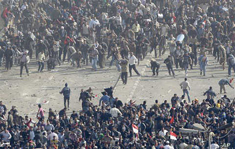 Pro-government demonstrators, below, and anti-government demonstrators, above, clash in Tahrir Square, the center of anti-government demonstrations, in Cairo, Egypt, February 2, 2011