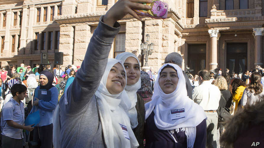 Mussarrat Rehman, from left, Rida Syed and Sadaf Karim take a selfie during Texas Muslim Capitol Day, Jan. 31, 2017, at the Texas Capitol in Austin, Texas.