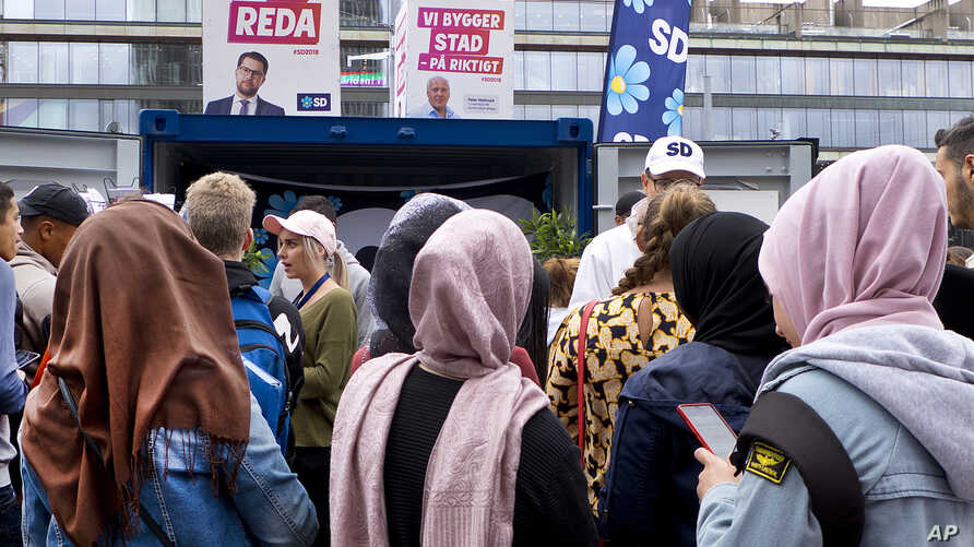 Young women listen to a party member of the right-wing Sweden Democrats in Stockholm, Sweden, Aug. 31, 2018.