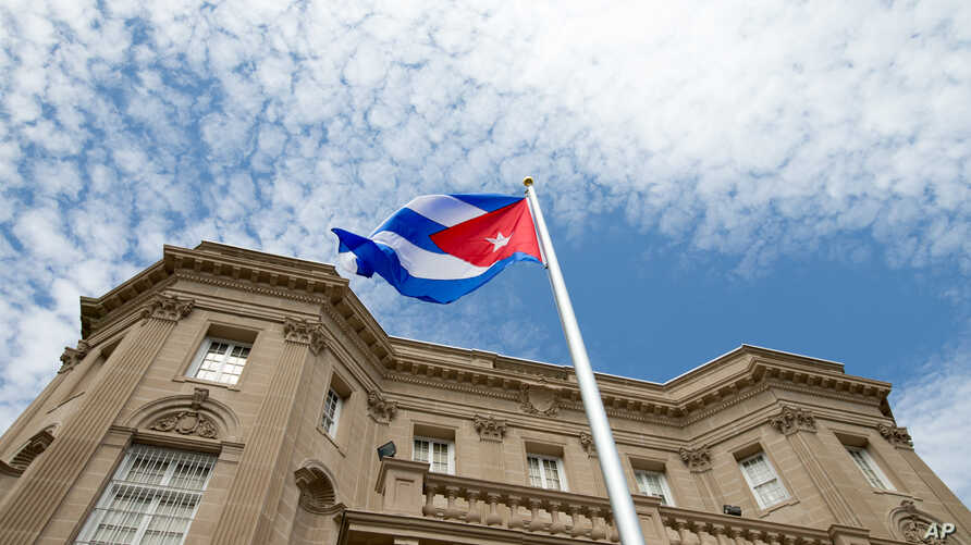 FILE - The Cuban flag is raised over their new embassy in Washington.