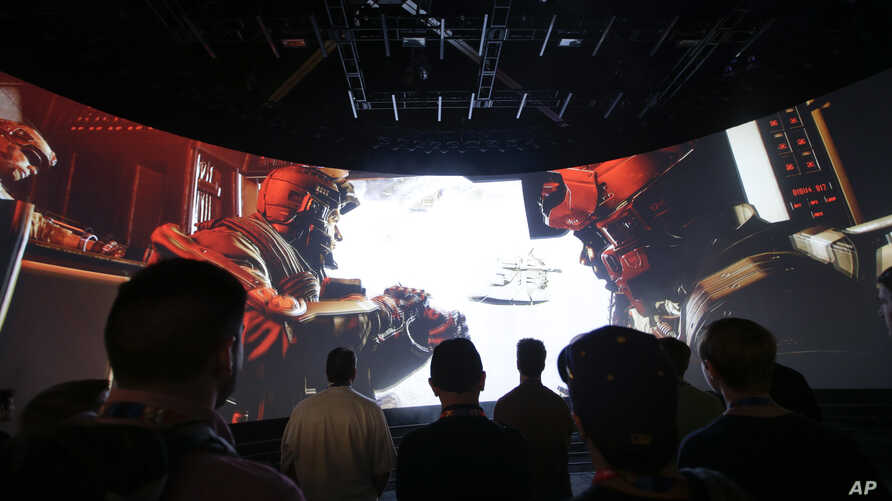 """People watch the """"Call of Duty: Advanced Warfare"""" video game trailer at the Activision booth at the Electronic Entertainment Expo in Los Angeles, June 12, 2014."""