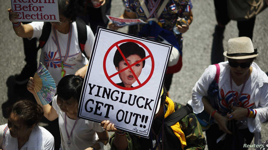 An anti-government protester carries a placard with a picture of Thai Prime Minister Yingluck Shinawatra as protesters march through central Bangkok March 29, 2014. Tens of thousands of Thai anti-government protesters rallied across Bangkok on Saturd