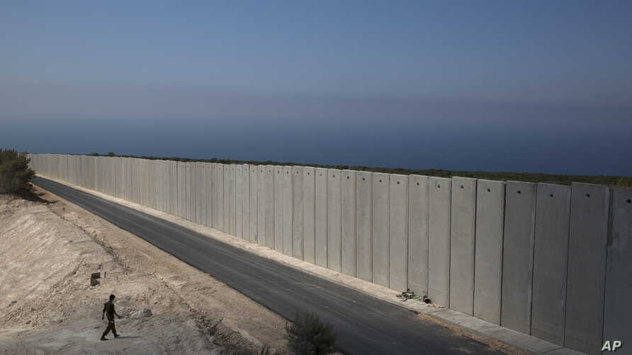 An Israeli soldier stands near a wall at the Israel Lebanon border near Rosh Haniqra, northern Israel. Even with attention currently focused on Gaza-based Hamas militants along its southern border, Israel's most pressing security concerns lie to the