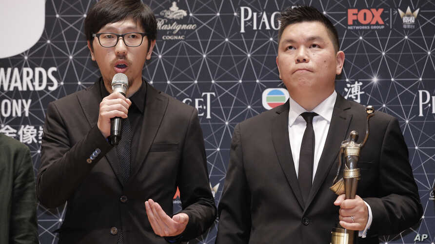 """Hong Kong movie producer Andrew Choi, right, and director Ng Ka-leung pose after winning the Best Film award for their movie """"Ten Years"""" during the Hong Kong Film Awards in Hong Kong, Sunday, April 3, 2016."""