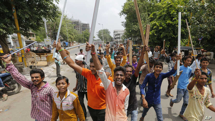 Members of India's low-caste Dalit community hold wooden sticks and shout slogans in Ahmadabad, India, July 20, 2016.