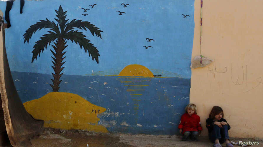 Syrian refugee girls sit in front of a painted wall in the Bab Al-Salam refugee camp in Azaz, near the Syrian-Turkish border, Oct. 27, 2014.
