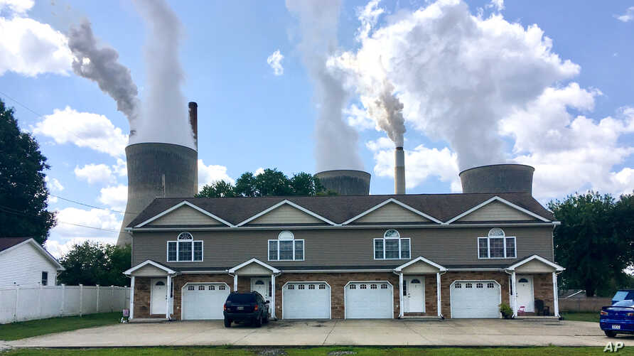 In this Aug. 23, 2018 photo, American Electric Power's John Amos coal-fired plant in Winfield, W.Va, is seen from an apartment complex in the town of Poca across the Kanawha River.