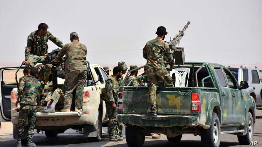 FILE - This photo released Sept 4, 2017, by the Syrian official news agency SANA shows Syrian troops and pro-government gunmen standing on pickup trucks with heavy machine guns mounted on them, in the eastern city of Deir el-Zour, Syria.