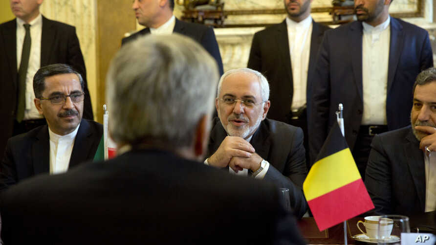 Iranian Foreign Minister Jawad Zarif (C-R) speaks with Belgian Foreign Minister Didier Reynders during a meeting at the Egmont Palace in Brussels on Jan. 11, 2018, amid doubts over the future of an international agreement curbing the Islamic Republic