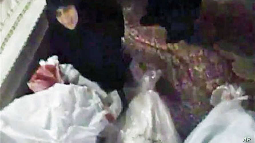 Image made from amateur video released December 27, 2011, purports to show a woman mourning over a relative who has been killed in Homs, Syria, December 26, 2011.