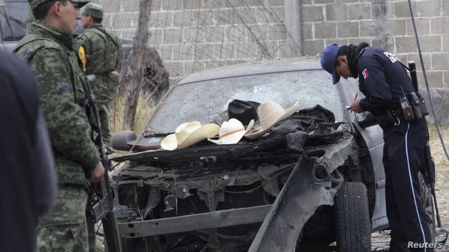 Soldiers and police inspect the site of an explosion in the village of Jesus Tepactepec, near the state capital Tlaxcala, Mar. 15, 2013.