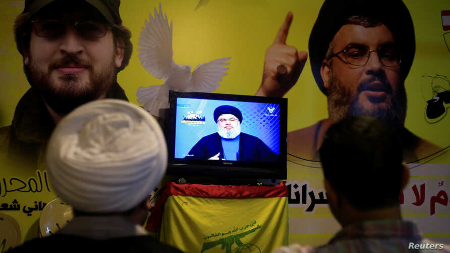A Shi'ite sheikh watches Lebanon's Hezbollah leader Sayyed Hassan Nasrallah speaking on television in Nabatieh in southern Lebanon, Aug. 4, 2017.