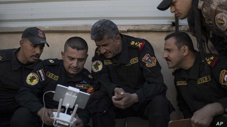 FILE - Iraqi special forces Lt. General Abdul-Wahab al-Saadi, center, looks at a live video feed from a drone flying over Islamic State militant-held territory as they advance their position in Mosul, Iraq, Nov. 18, 2016.