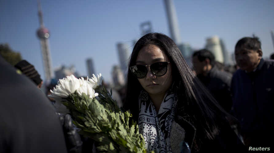 A woman offers flowers during a memorial ceremony in memory of people who were killed in a stampede incident during a New Year's celebration, on the Bund in Shanghai, Jan. 1, 2015.