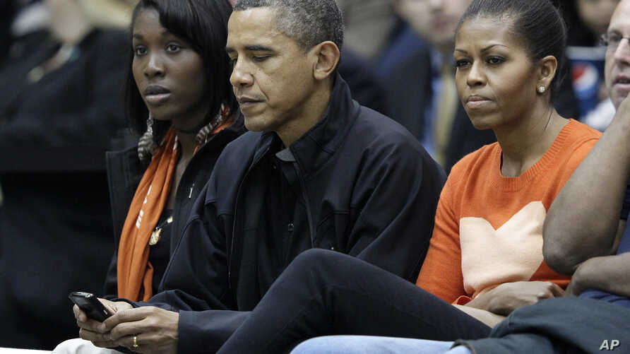 FILE - President Barack Obama, alongside first lady Michelle Obama, checks his BlackBerry as they watch a basketball game in Towson, Maryland, Nov. 26, 2011.