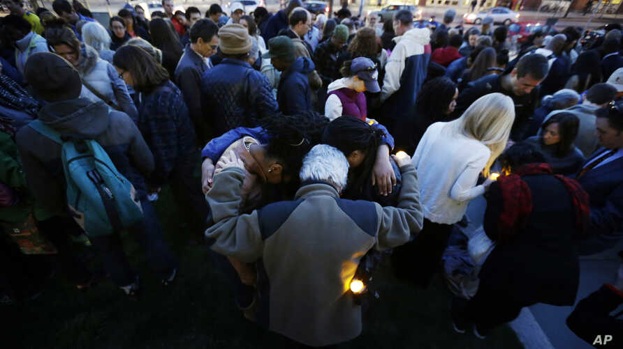 Mourners pray during a candlelight vigil in the aftermath of Monday's Boston Marathon explosions, April 17, 2013, at City Hall in Cambridge, Mass.