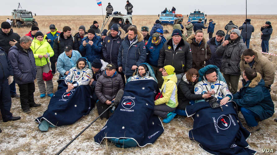 Russian cosmonauts Mikhail Kornienko, left, Sergey Volkov of Roscosmos, center, and Expedition 46 Commander Scott Kelly of NASA, rest in chairs outside of the Soyuz TMA-18M spacecraft just minutes after they landed in a remote area near the town of Z