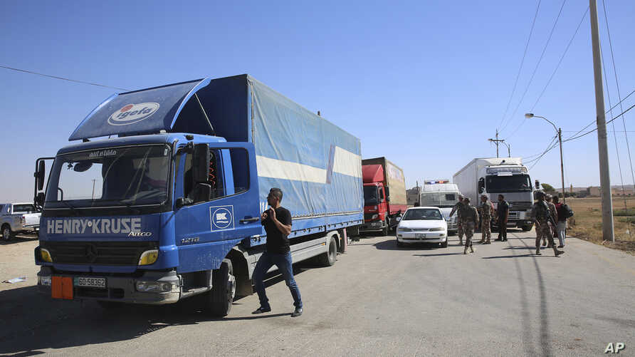 Trucks laden with aid for displaced Syrians wait to cross from Jordan to the Syrian side of the border, in Jabir As Sirhan, Jordan, July 1, 2018.