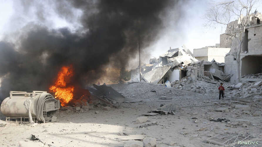 A boy stands on rubble at a site hit by what activists said was a barrel bomb dropped by forces loyal to Syria's President Bashar al-Assad in the al-Maadi neighborhood of Aleppo, June 20, 2014.