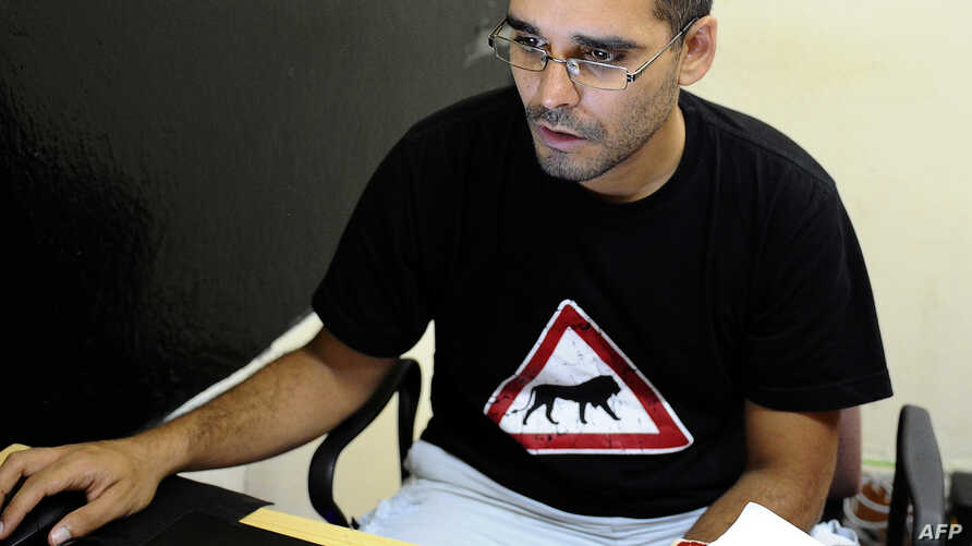 FILE - Angolan activist Luaty Beirao works on his laptop on in Luanda, Aug. 30, 2012.